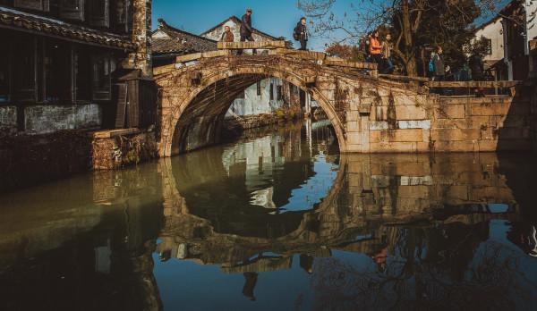 美国有线电视新闻网,也就是俗称的CNN,似乎对中国的旅游景点特别感兴趣,它评定的中国四大最美的水乡,江苏周庄古镇,是江南地区唯一上榜的水乡。  CNN的评语比较有意思:尽管周庄将自己标榜为中国最古老的水乡尚存质疑,但这个建于1086年的村庄,以其纵横交错、灯笼成荫的运河,在昭示着中国浪漫的过去。  1086年,是中国北宋元祐的元年,据说当时有位叫周迪公郎的人,在这片四面环水的孤岛上,经农设庄,并捐资修了一座寺庙。当地百姓为了感激周迪公,便把这块地方叫做周庄。  周庄,地处江苏的苏州,同上海交界