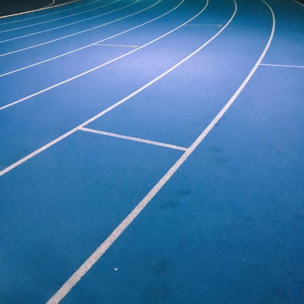 蓝色的塑胶跑道,跑道周围是各种运动场地,学生社团有组织地进行体育