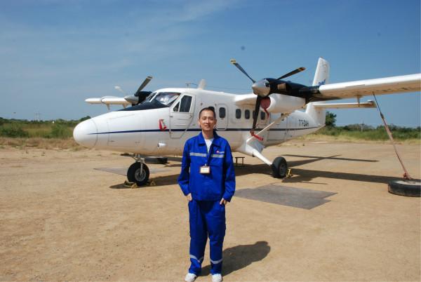 照片是我当时乘坐的小型飞机前往ronier,身穿中石油的制服,脖子上挂着